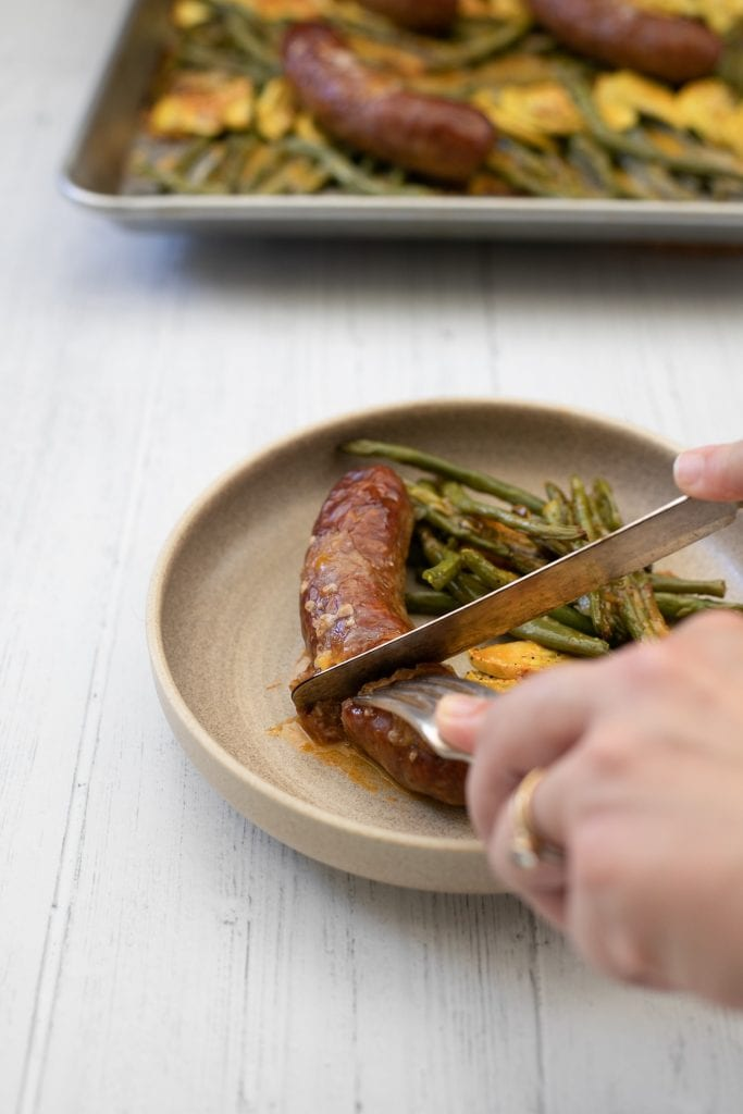 Knife cutting sausage with green beans from a sheet pan dinner