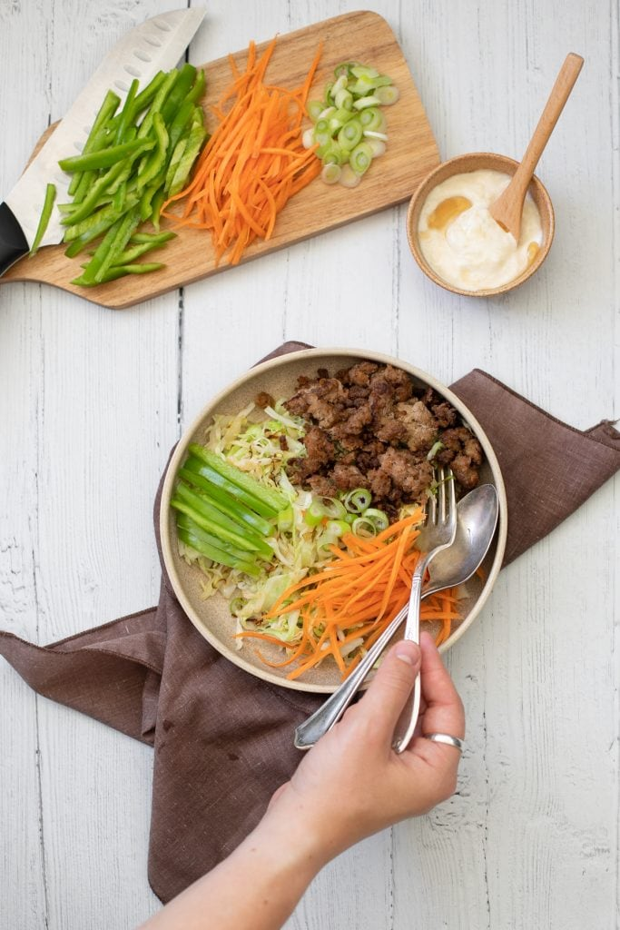 Turkey Cabbage Asian bowl with ground turkey, shredded cabbage, julienned carrots, and sliced bell peppers. An easy low carb Asian bowl recipe.