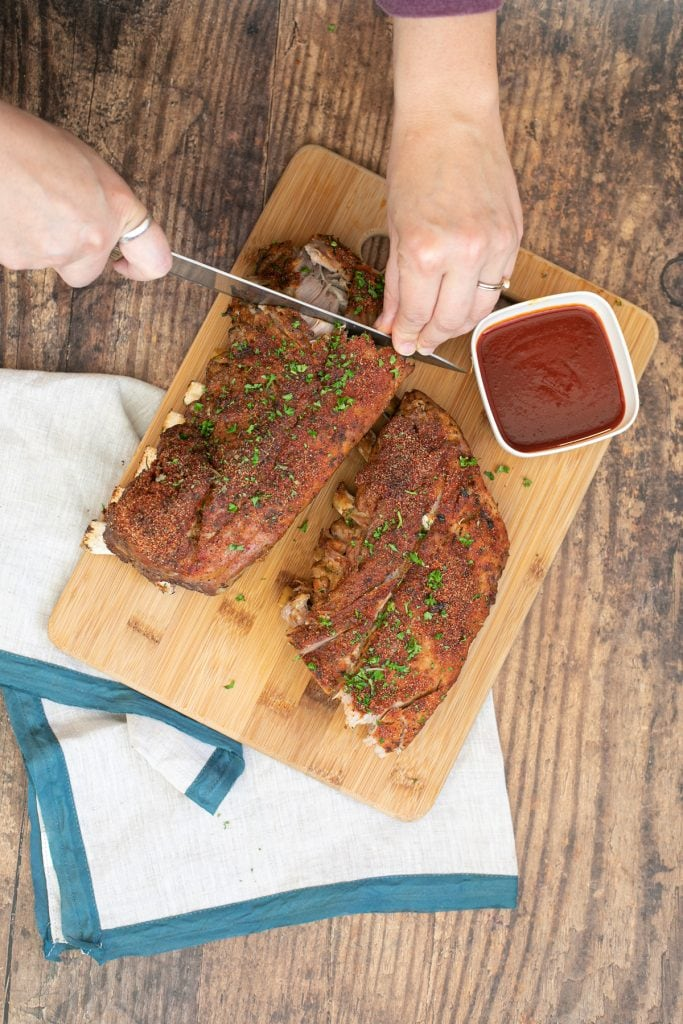 Cutting low carb ribs on a cutting board - ribs made with keto diy rub.