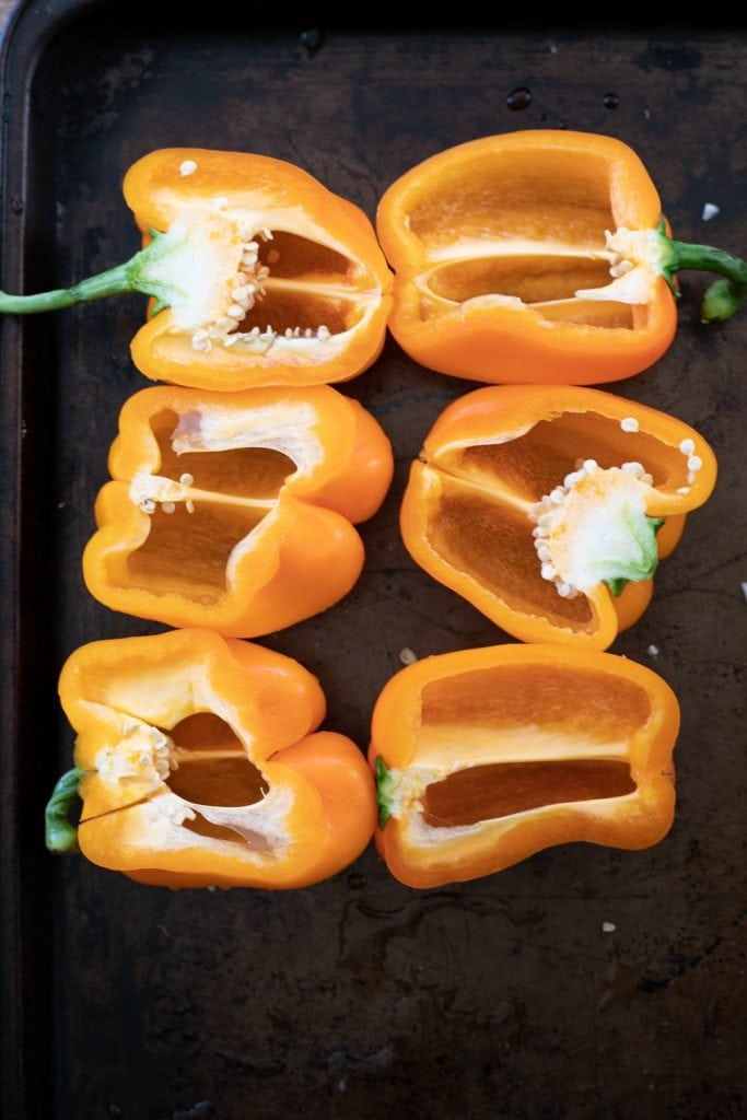 Bell peppers for stuffed bell peppers. Cut the bell peppers in half, lengthwise then clean the seeds and fibers out.