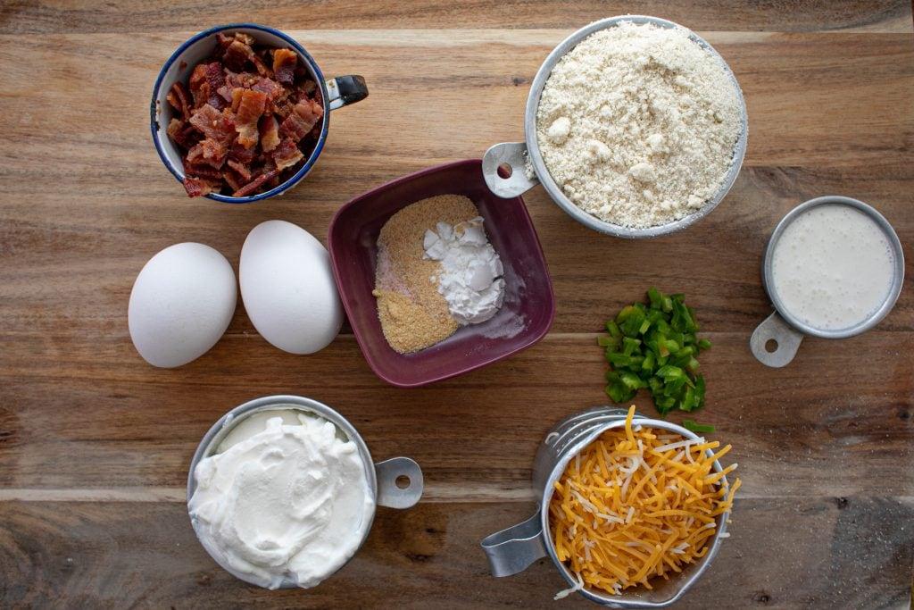 Ingredients to make Keto Jalapeno popper muffins - Bacon, eggs, cheese, almond flour, half and half, sour cream, butter, garlic powder, onion powder, salt, baking powder, jalapenos