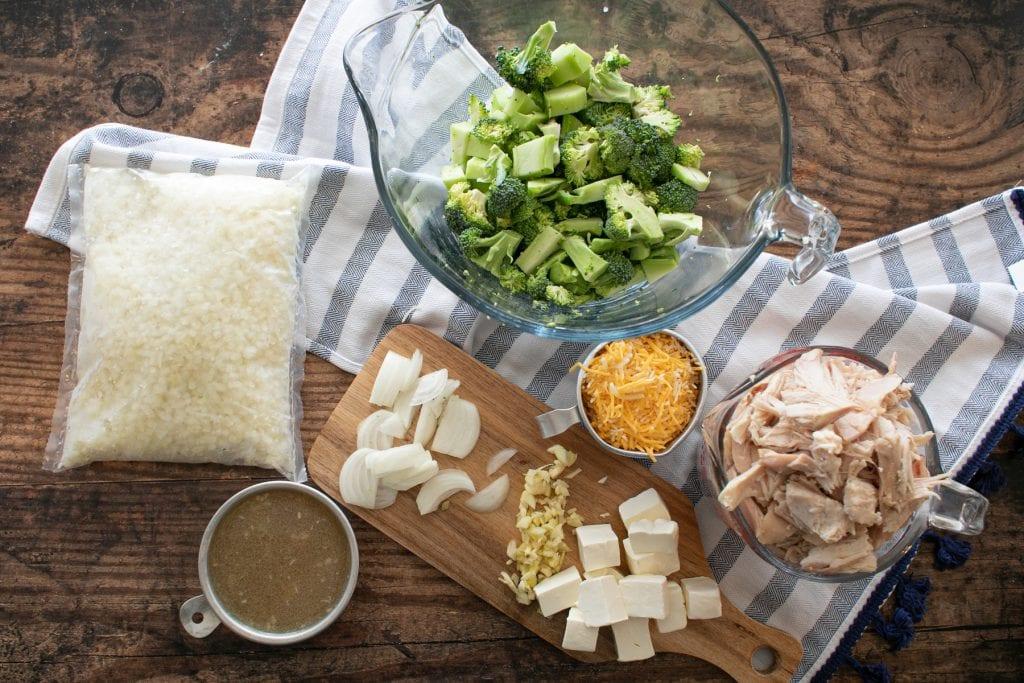 Ingredients for making keto chicken broccoli rice casserole in the Instant Pot : cooked chicken, broccoli, cauliflower rice, onions, garlic, cream cheese, shredded cheese, chicken stock, salt
